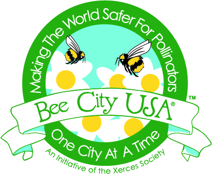 The Bee City USA logo, which has a dark green circle around a stylized scene with bees and white flowers. A banner across it says