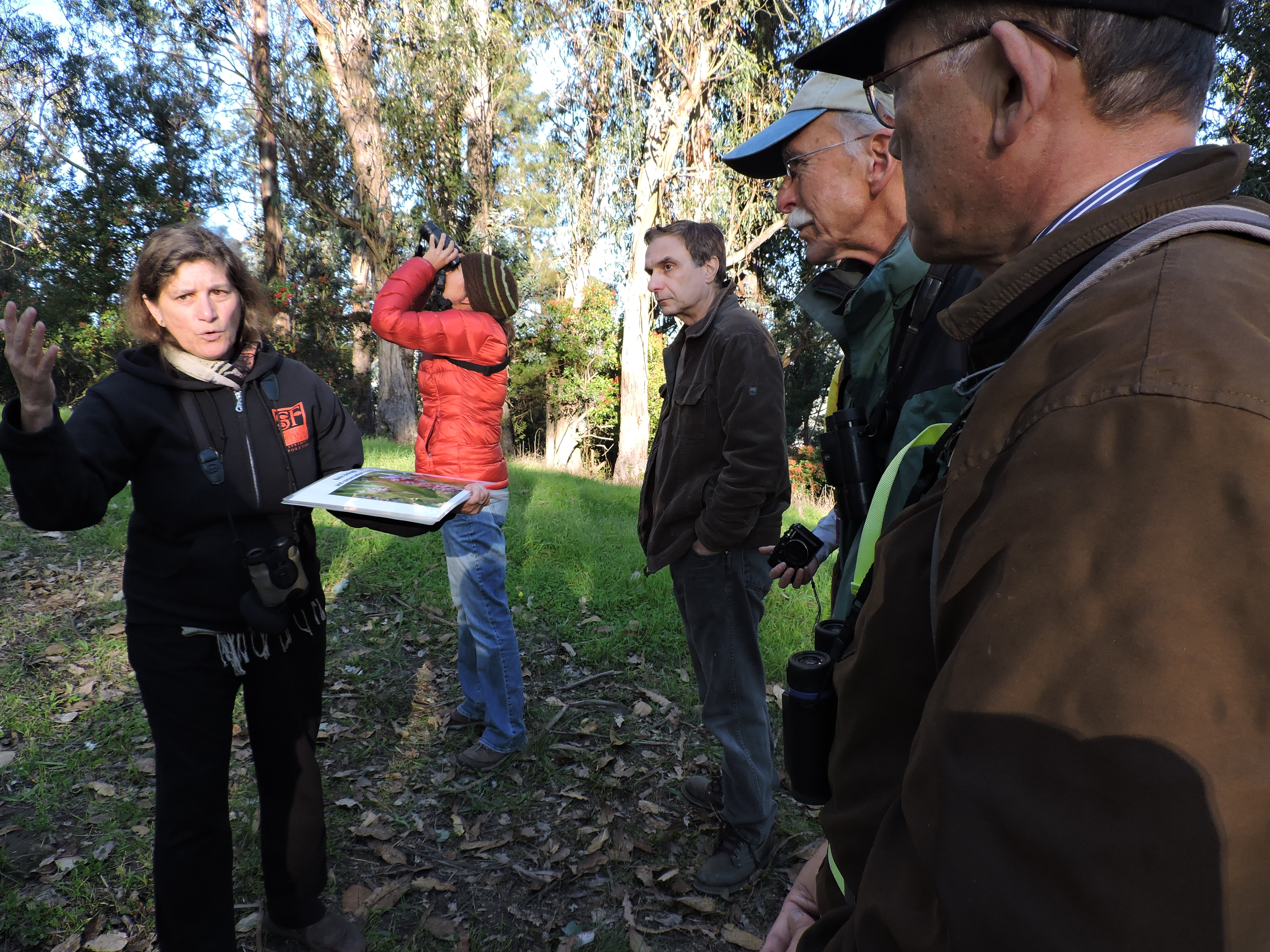 A woman in a dark coat (left) speaks to an assembled group of volunteers (right) in a wooded setting.