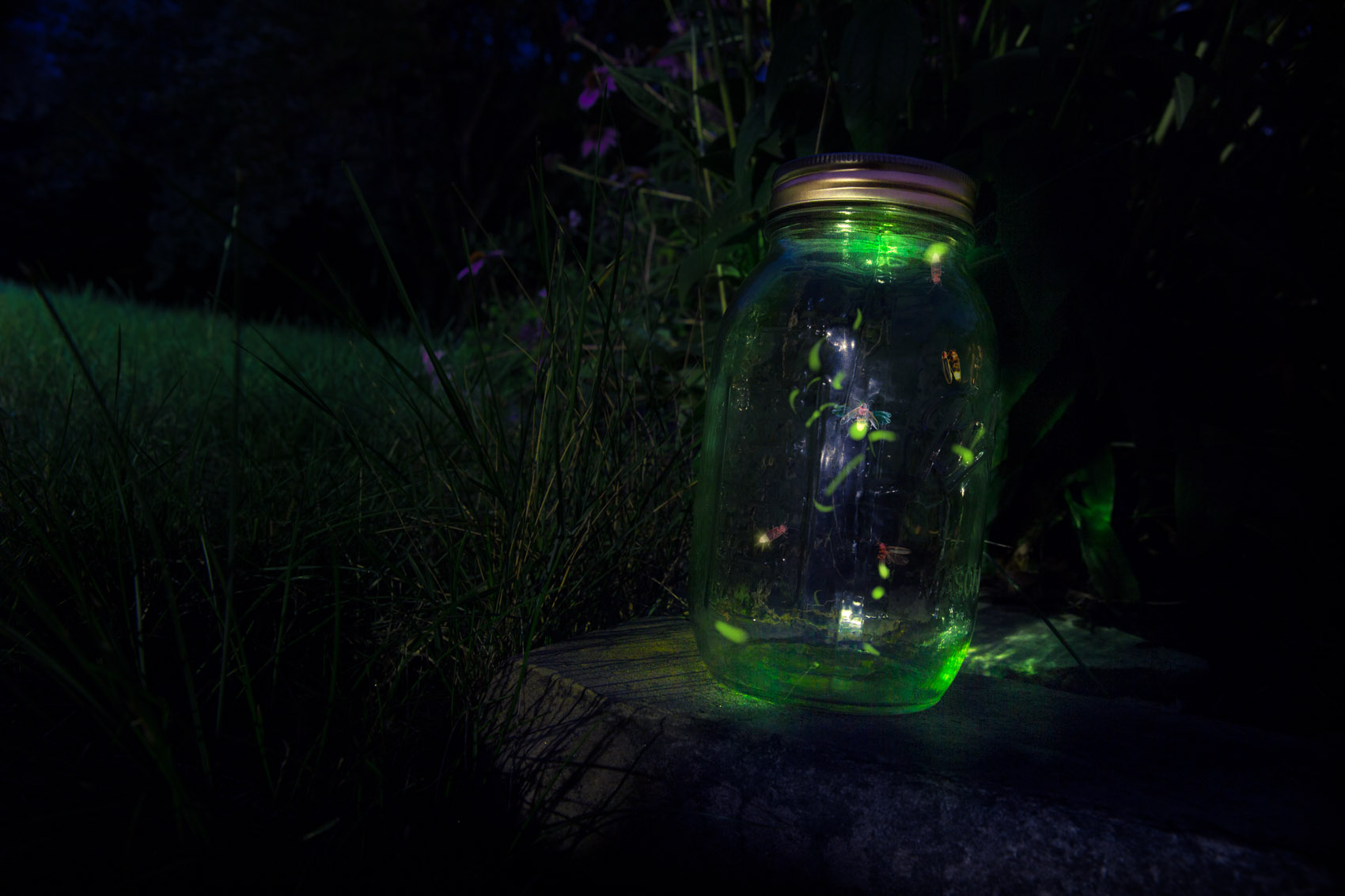 A glowing green mason jar contains a few fireflies in flight.