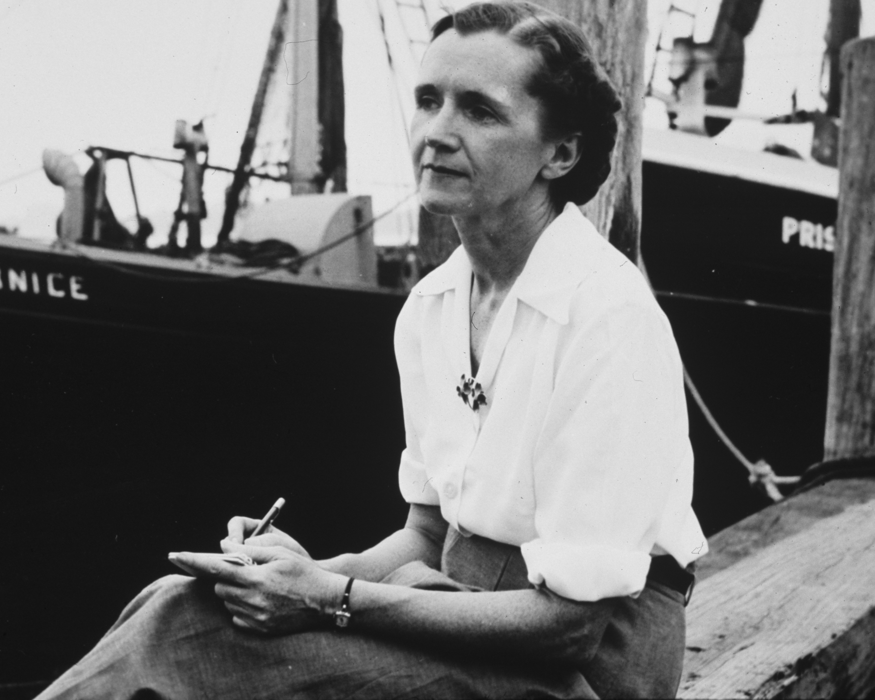 Rachel Carson sits with pen in hand on a dock, with a boat behind her, in this black-and-white historic photo.