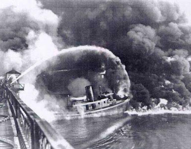 A firefighter sprays water from a bridge onto the burning Cuyahoga River in this historical photo, in black and white..