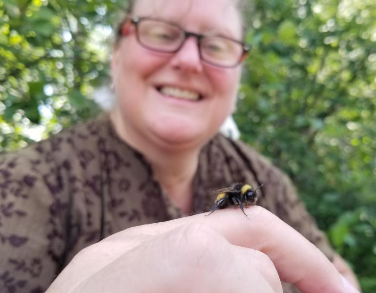 A woman smiles while looking at a fuzzy, black, and yellow bumble bee on her finger.