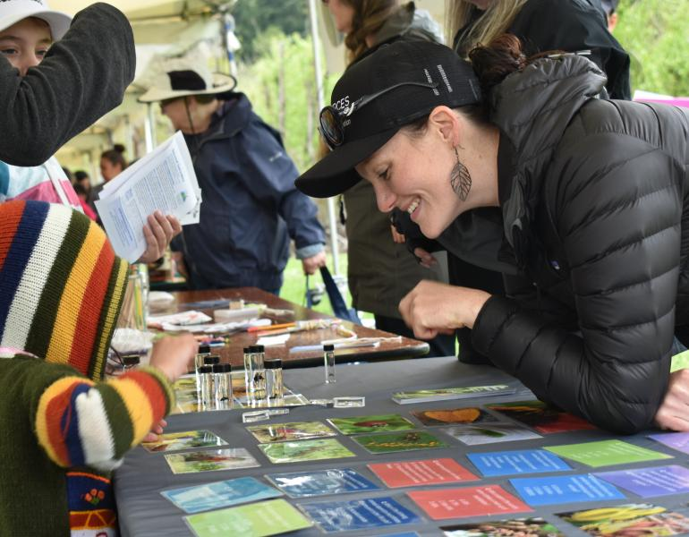 A smiling woman wearing a black coat and a black Xerces Society hat leans over a table. On the other side of the table, a kid with a colorful hoodie reaches for an assortment of small glass vials containing bee specimens. The woman and the kid are looking at the same vials and appear to be talking.