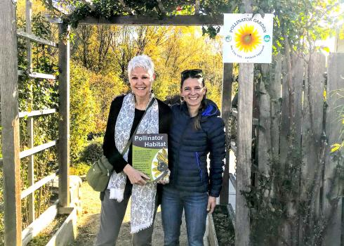 A tall woman with short, white hair who is holding a Xerces pollinator habitat sign stands next to a woman with dark hair and a dark down coat, in the entrance to a garden.