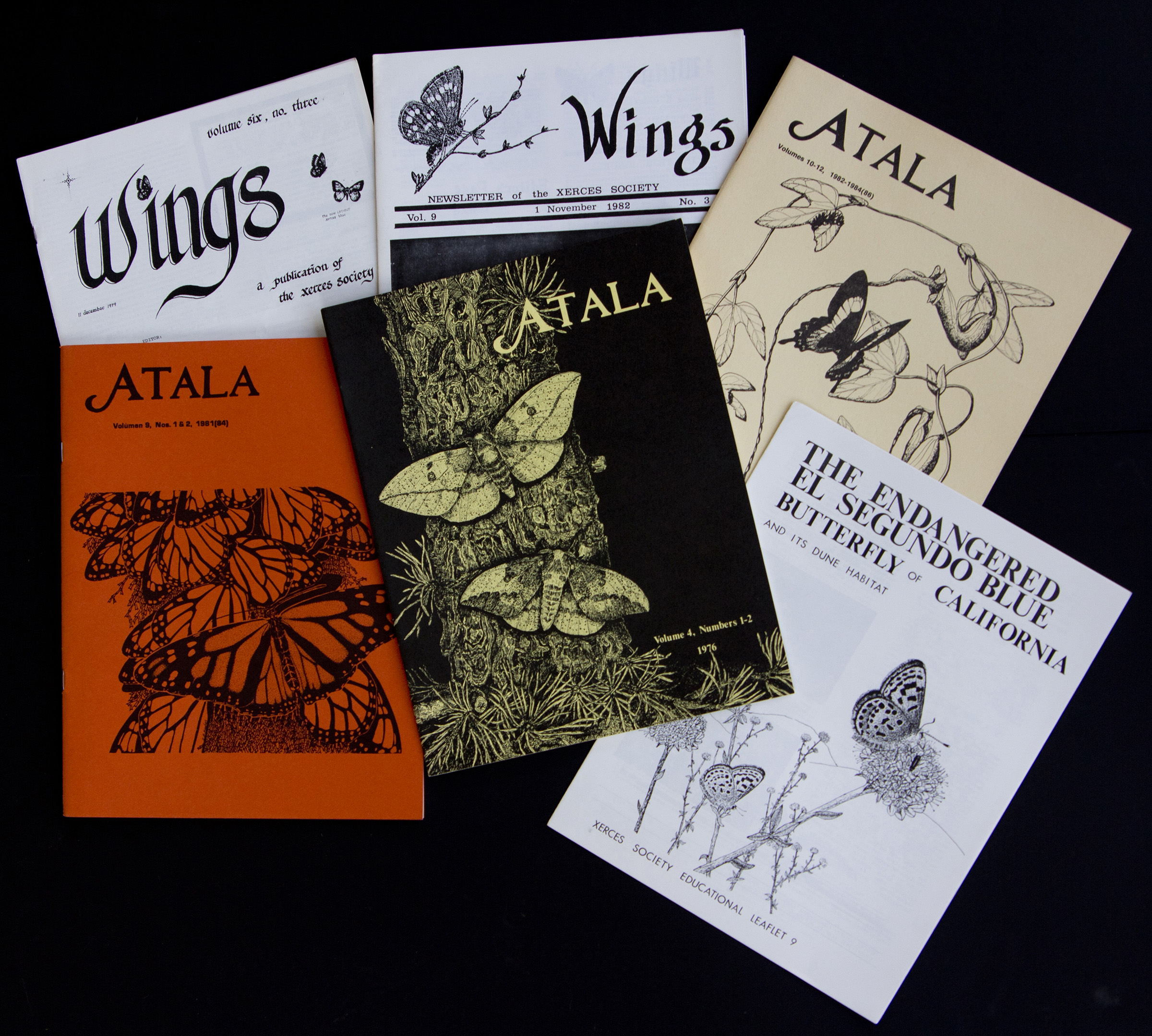 A selection of old publications: Wings newsletter is printed in black-and-white, with the covers of Atala journal are orange, black, and pale yellow.