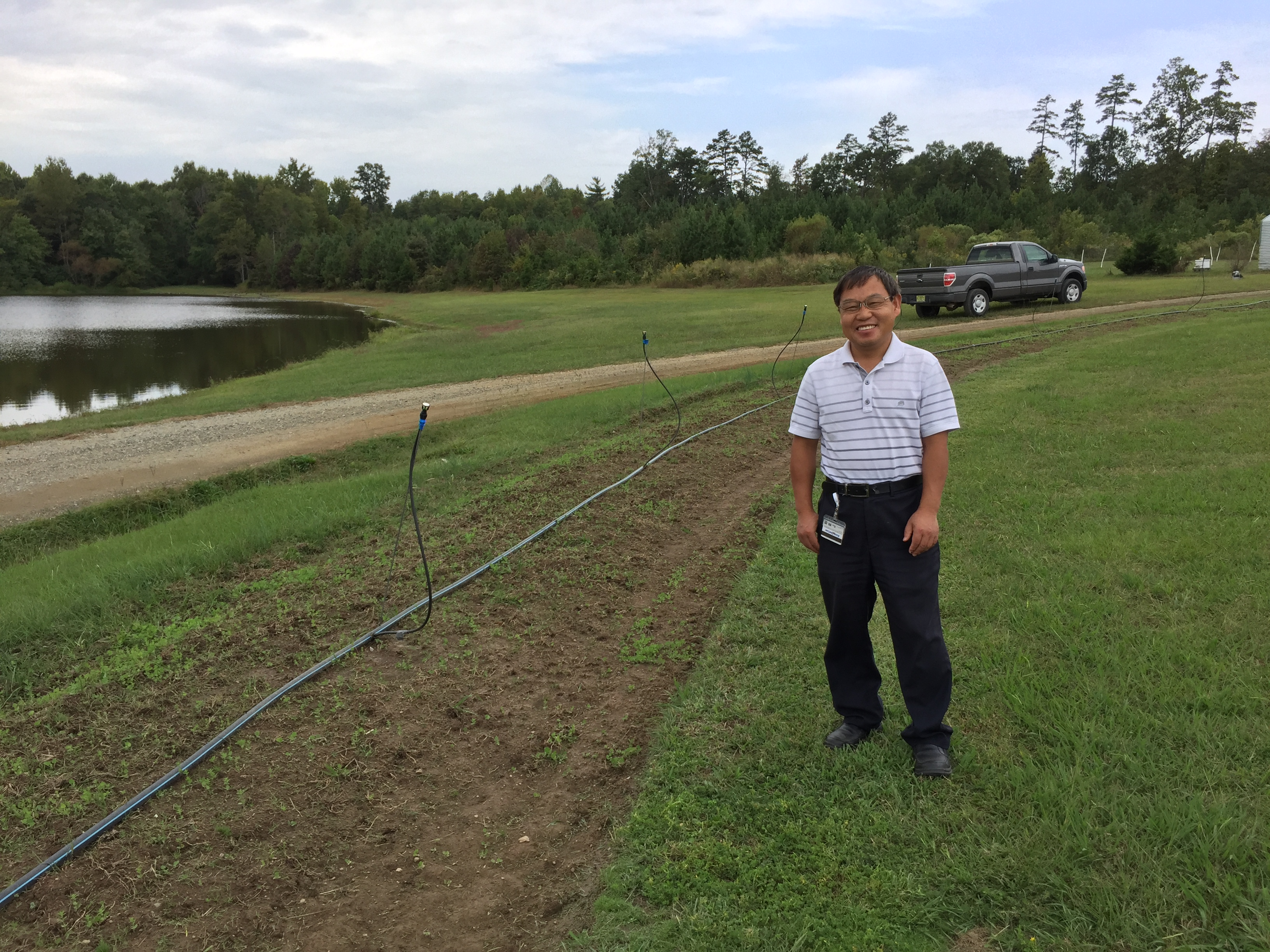 A smiling man stands near the hedgerow-to-be, currently a bed of soil with small plants and some irrigation set up.