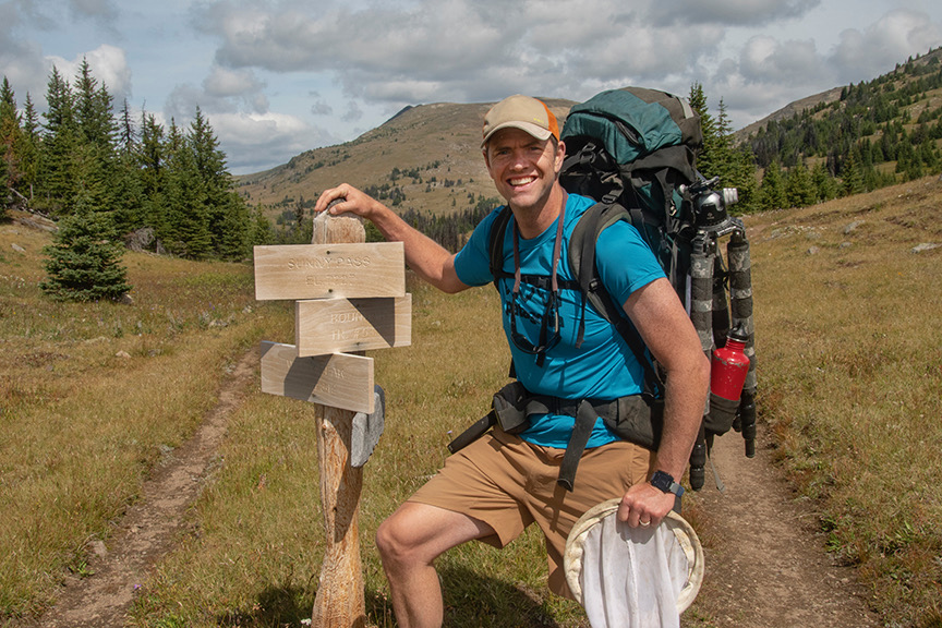 The author grins as he poses by a wooden trail sign, with a mountain in the background. He is carrying a big backpack and holding a net.