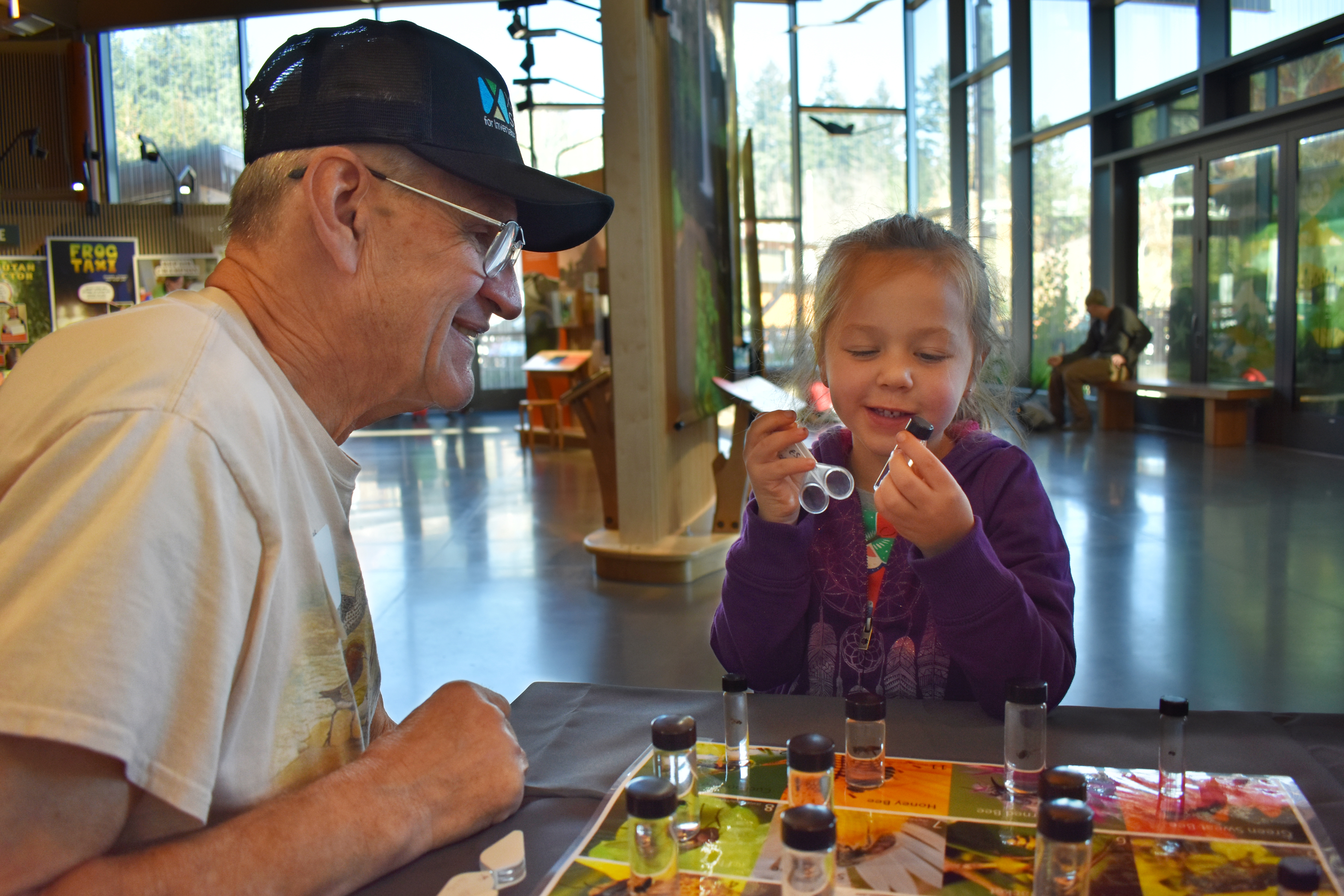 A Xerces volunteer talking with a little girl about bees at a table as she hols a magnifying glass.