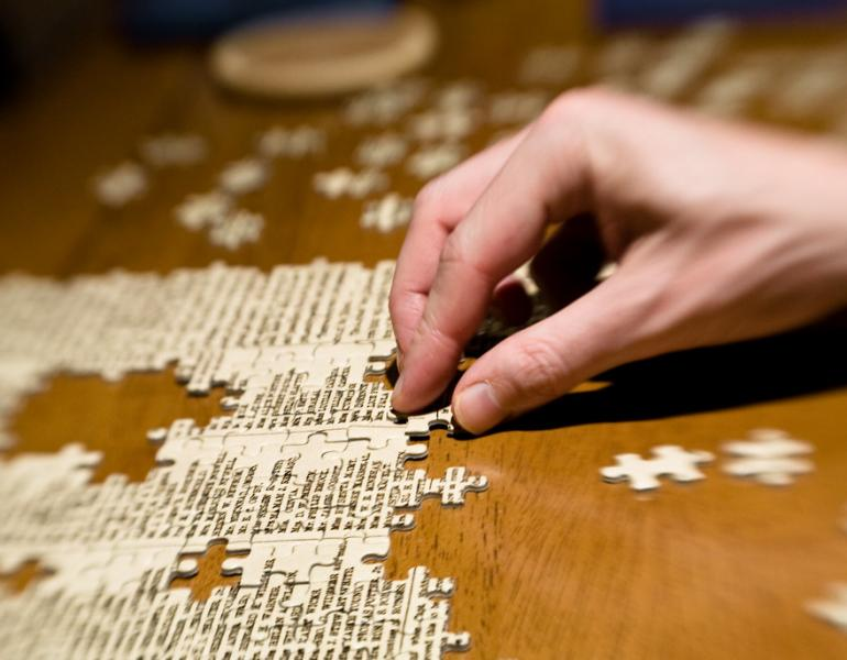 Pieces of a puzzle are being assembled on a dark, wooden table. A hand moves the pieces.