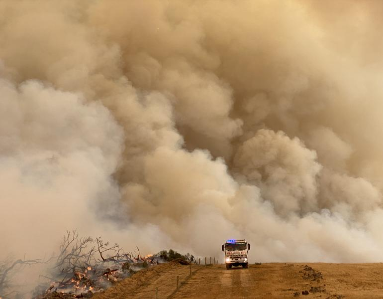 Fire truck drives across a burning landscape, with the sky full of brown smoke