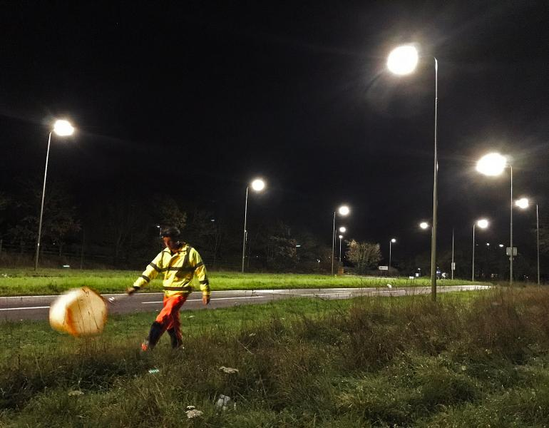 A person wearing fluorescent clothing and a headlamp swings a net alongside a roadway lit by streetlamps at night.