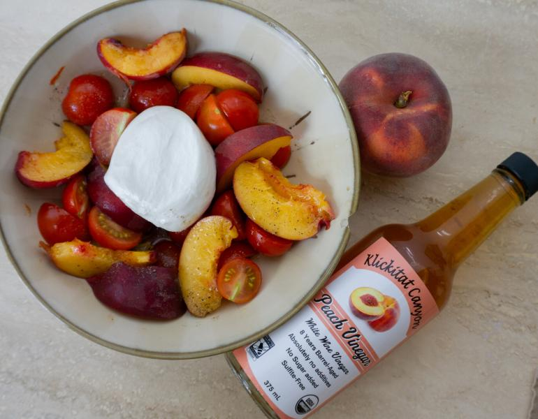 A bottle of vinegar lies on a table beside a bowl full of slices of peach and cherry tomatoes