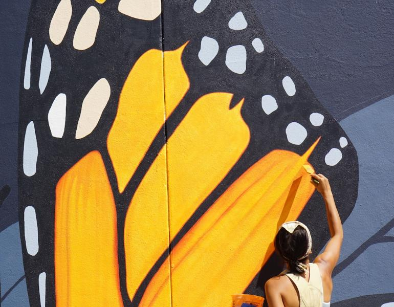 Artist Jane Kim of Ink Dwell studio paints the wing of a giant monarch butterfly, part of the Midnight Dream mural in downtown Orlando, Florida.