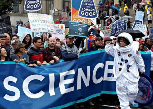 "A crowd at a demonstration holds up a banner with the letters ""CIENCE"" visible across its length."
