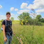 Sarah Nizzi standing in a prairie on a sunny day
